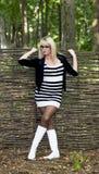 有白色起动的金发碧眼的女人在wattled篱芭 库存照片