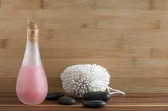 有白色身体洗气器和黑岩石的桃红色液体皂 免版税库存图片