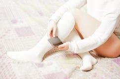 有白色长袜的妇女在床上 图库摄影