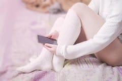 有白色长袜的妇女在床上 库存照片