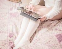 有白色长袜的妇女在床上 免版税图库摄影