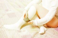 有白色长袜的妇女在床上 免版税库存照片