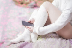 有白色长袜的妇女在床上 库存图片