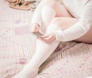 有白色长袜的妇女在床上 免版税库存图片