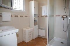 有白色陶瓷装置和阵雨客舱的现代卫生间 免版税库存照片