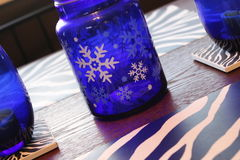 有白色雪花和斑马的蓝色玻璃瓶子镶边装饰 免版税库存照片
