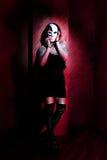 有白色面具的女孩在红色背景 图库摄影
