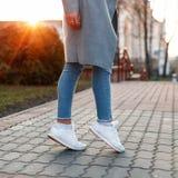 有白色鞋子和牛仔裤的美好的女性腿在日落 免版税库存图片