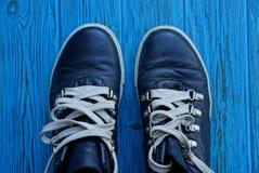 有白色鞋带的两双黑鞋子在一个蓝色委员会 库存图片