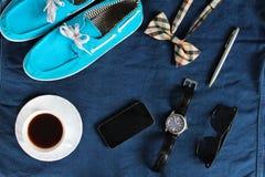有白色鞋带的,橙色方格的bowtie,电话,茶偶然蓝色鞋子在深蓝牛仔裤背景的 顶视图 平的位置 免版税库存照片