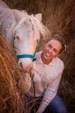 有白色鬃毛小马的美女 休息在下降的一个干草堆下午 库存图片