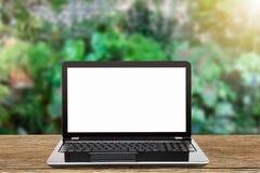 有白色黑屏的膝上型计算机在被弄脏的庭院背景的葡萄酒木桌上 库存图片
