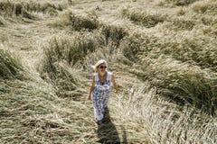 有白色,蓝色礼服的性感的妇女审阅黑麦领域 库存照片