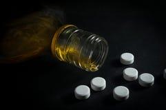 有白色医学药片的威士忌酒瓶 免版税库存照片
