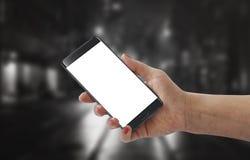 有白色黑屏的女孩展示现代黑巧妙的电话大模型的 免版税库存图片