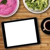 有白色黑屏的数字式片剂在饭桌 库存照片