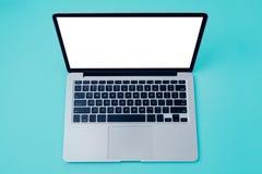 有白色黑屏的膝上型计算机在蓝色背景 在视图之上 免版税库存照片
