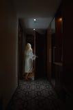 有白色浴巾的赤足妇女打开门 免版税库存照片