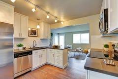 有白色细木家具的新近地被改造的厨房室 免版税库存图片