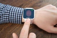 有白色smartwatch的男性手与在scree的一个指纹 免版税库存图片