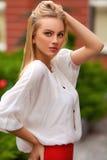 有白色T恤杉和金发摆在的美丽的性感的妇女室外 背景在纵向射击工作室白色的方式女孩 库存照片