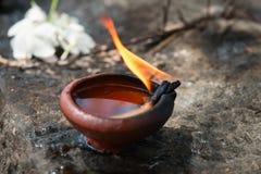 有白花的灼烧的黏土油灯一佛教和印度te 免版税库存照片