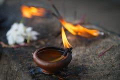 有白花的灼烧的黏土油灯一佛教和印度te 免版税库存图片