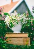有白花的陶瓷杯子在堆在清洁的旧书用反对村庄房子的背景的开花的草本 免版税图库摄影