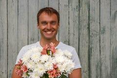 有白花的年轻愉快的人在木背景 免版税库存照片