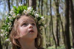 有白花花圈的迷人的女婴在她的头的,当走在一个晴朗的下午时的森林里 免版税库存照片