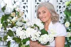 有白花花束的资深妇女  免版税图库摄影