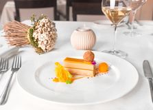有白酒酒杯的熟食店鹅肝和芒果在餐馆桌上 免版税库存图片