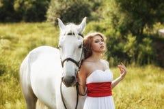 有白马的美丽的肉欲的妇女 免版税图库摄影