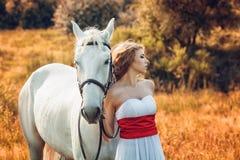 有白马的美丽的肉欲的妇女 免版税库存照片