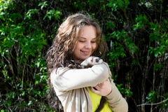 有白鼬的快乐的女孩在手上 免版税库存照片