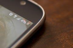 有百分之四电池充电的智能手机在屏幕上 免版税库存图片