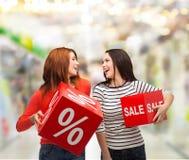 有百分之的微笑的十几岁的女孩和销售签字 免版税库存图片