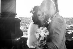 有百合花束的新娘微笑,当huged由t的时未婚夫 免版税库存照片
