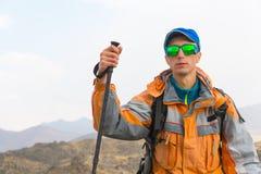 有的一个人在膜夹克的佩带的太阳镜,盖帽,有一个背包和棍子的北欧走的,旅客 免版税图库摄影