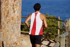 有的一个高人体育在小山的早晨凹凸部计算在海岸运动服的英俊的人参与奔跑的A,主角附近 库存照片