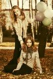有的两个时尚青少年的女孩气球在秋天停放 免版税库存图片
