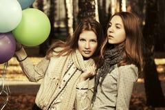 有的两个时尚青少年的女孩气球在秋天停放 图库摄影