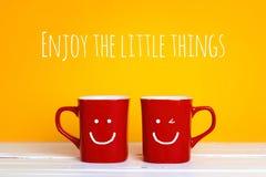 有的两个红色咖啡杯在黄色背景的微笑的面孔 库存图片