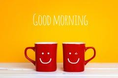 有的两个红色咖啡杯在黄色背景的微笑的面孔 免版税库存照片
