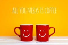 有的两个红色咖啡杯在黄色背景的微笑的面孔 图库摄影