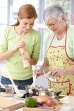 有的乐趣厨房微笑的妇女 免版税库存照片