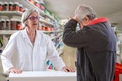 有的人头疼谈话与药剂师,当购物止痛药在地方药房时 免版税库存照片