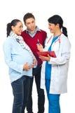 有的医生与怀孕的夫妇的交谈 免版税图库摄影