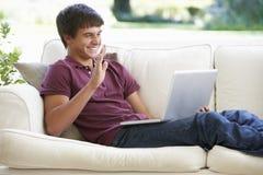 有的十几岁的男孩在膝上型计算机的录影电话在家 图库摄影