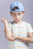 有的受伤的男孩被挫伤的手肘在痛苦中起反应 免版税库存图片
